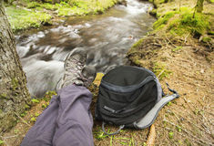 Hiker Resting in the Forest next to River Stock Photo