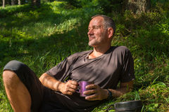 Hiker is resting in the green grass Stock Images