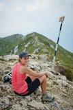 Hiker resting on mountain peak Royalty Free Stock Image