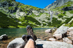 Hiker resting over the glacier lake and waterfall Stock Photos