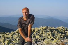 Hiker resting of a rocky top at a wonderful sunny morning. Royalty Free Stock Photo