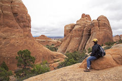 Hiker resting on a trail at the Devils Garden at Arches National Park in Moab Utah. Stock Photo