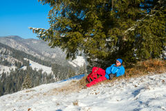 Hiker resting under a fir-tree in winter mountains Royalty Free Stock Image