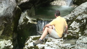 Hiker resting at a waterfall stock video