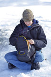 Hiker Resting. A young hiker searches his backpack for a snack while resting on a snowy bank stock photos