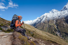 Hiker rests on trek in Himalayas Royalty Free Stock Photography