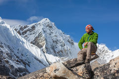 Hiker rests on trek in Himalayas Royalty Free Stock Photos