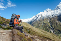 Hiker rests on trek in Himalayas Stock Photography