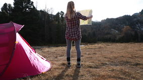 Hiker returns to tent, checks map at sunset stock video