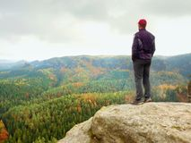 Hiker on rock end above valley. Man watch over misty and autumnal morning valley to bright morning Sun. Stock Photos
