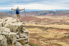 Hiker on rocky cliff overlooking valley Stock Images