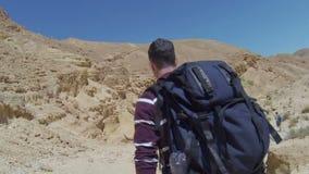 Hiker in rocky desert stock video