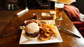 A hiker`s burger dinner in a Pub. With chips & Beer stock images