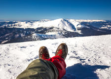 Hiker's legs relax duridg winter hiking. Beautiful winter nature at sunny day in mountains Royalty Free Stock Images