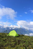 Hiker s tent on the high mountain, with snow mountains in the background Royalty Free Stock Image