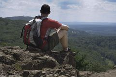 Hiker's View. A hiker takes a rest at the top Stock Image