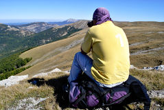 Hiker seating on backpack Royalty Free Stock Images
