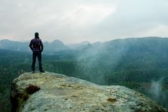 Hiker on sharp cliff of sandstone rock in rock empires park and watching over misty and foggy spring valley Royalty Free Stock Photo