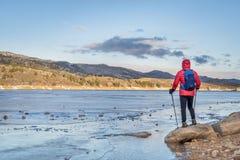 Hiker at shore of frozen mountain lake Stock Photo