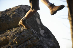 Hiker in shorts and hiking boots leaping from rock, low section, close-up (blurred motion) Royalty Free Stock Photography