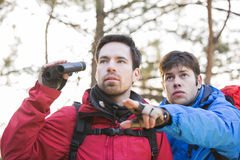 Hiker showing something to friend holding binoculars in forest Royalty Free Stock Photos