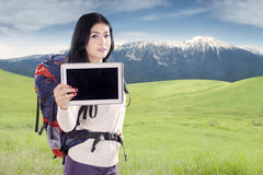 Hiker showing tablet in nature Royalty Free Stock Images