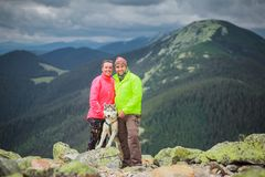 Hiker with siberian husky dog view in mountains. Hiker with siberian husky dog looking at beautiful view in mountains Stock Photos