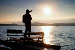 Hiker silhouette with backpack on abandoned  pedal boat in the sunset. Autumn sun above  sea Stock Images