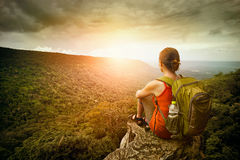 Hiker sits on the edge of the cliff and enjoying sunrise royalty free stock photo