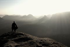 Hiker Sits On A Rocky Peak And Enjoy The Mountains Scenery Royalty Free Stock Photo