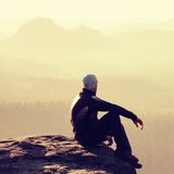 Hiker sits on a rocky peak and enjoy the mountains scenery Stock Image