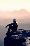 Hiker sits on a rocky peak and enjoy the mountains scenery Stock Images