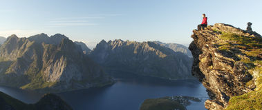 Hiker sitting above rocky landscape- Lofoten Islands, Norway Royalty Free Stock Images
