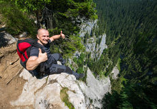 Hiker sitting on the edge of a very high cliff Stock Photos