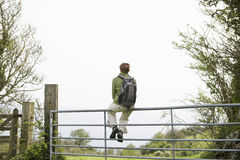 Hiker Sitting On Gate While Looking At View Stock Photography