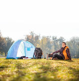 Hiker sitting on grass next to a tent Stock Photography