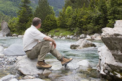 Hiker sitting at a mountain creek Stock Image