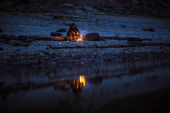 Hiker sitting near camping fire at river shore. Concept of loneliness, choice, silence. Shot of a hiker at the dawn sitting near the camping fire. Concept of Royalty Free Stock Images