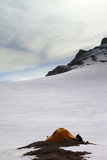 Hiker sitting near camping tent in evening snow mountains Stock Photography