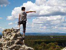 Hiker sitting near edge. Hiker on mountain pointing  towards something in the distance from a cliff's edge Stock Photography