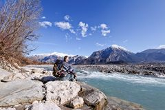 Hiker sitting on river shore, looking the mountains landscape. Hiker sitting on river shore over the rocks, looking the mountains landscape.Alps,Italy,Friuli Royalty Free Stock Photo