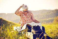 Hiker sitting in the sun with map Stock Image