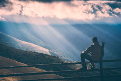 Hiker sitting on a wooden fence. Instagram stylisation. Hiker sitting on a wooden fence and enjoy rays of sunlight, shining through the clouds to the mountain Stock Images