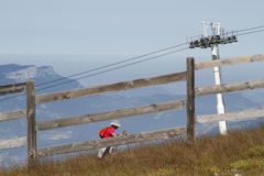 Hiker among the ski lift in summer. CHAMROUSSE, FRANCE, August 8, 2016 : A lonely hiker climbs among the ski slopes in Chamrousse mountain range Stock Photography