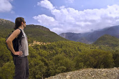 Hiker with small backpack in mountains. Young man in shorts and with bachpack looks at faraway mountains covered with clouds Stock Photography