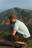 Hiker smokes on the top of the mountain. Tourist on the top of the mountain enjoys beautiful view Royalty Free Stock Images