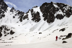 Hiker in snow mountain with trace from avalanches at sun spring Stock Photo