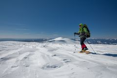 Hiker snowshoeing in winter mountains during sunny day.  Royalty Free Stock Photography