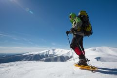 Hiker snowshoeing in winter mountains during sunny day.  Stock Photos