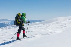 Hiker snowshoeing in winter mountains during sunny day.  Stock Image